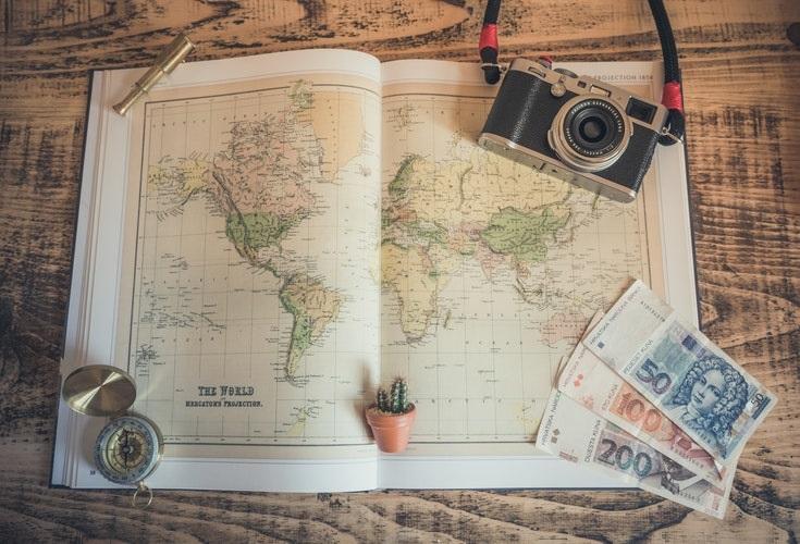 Imagen con mapa, una cámara fotográfica, una brújula y dinero,